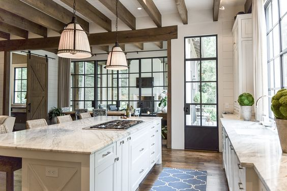 here they stuck with a white kitchen but the metal door windows dark beams and industrial lighting have a unique farmhouse look - Modern Farmhouse Kitchen